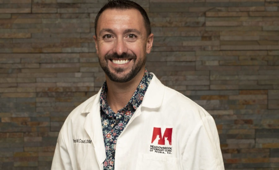 Chris Couri, DVM in front of stone wall.